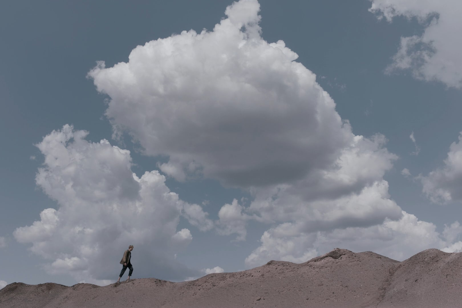 Man walking on a sand dune against the horizon beneath giant white clouds.