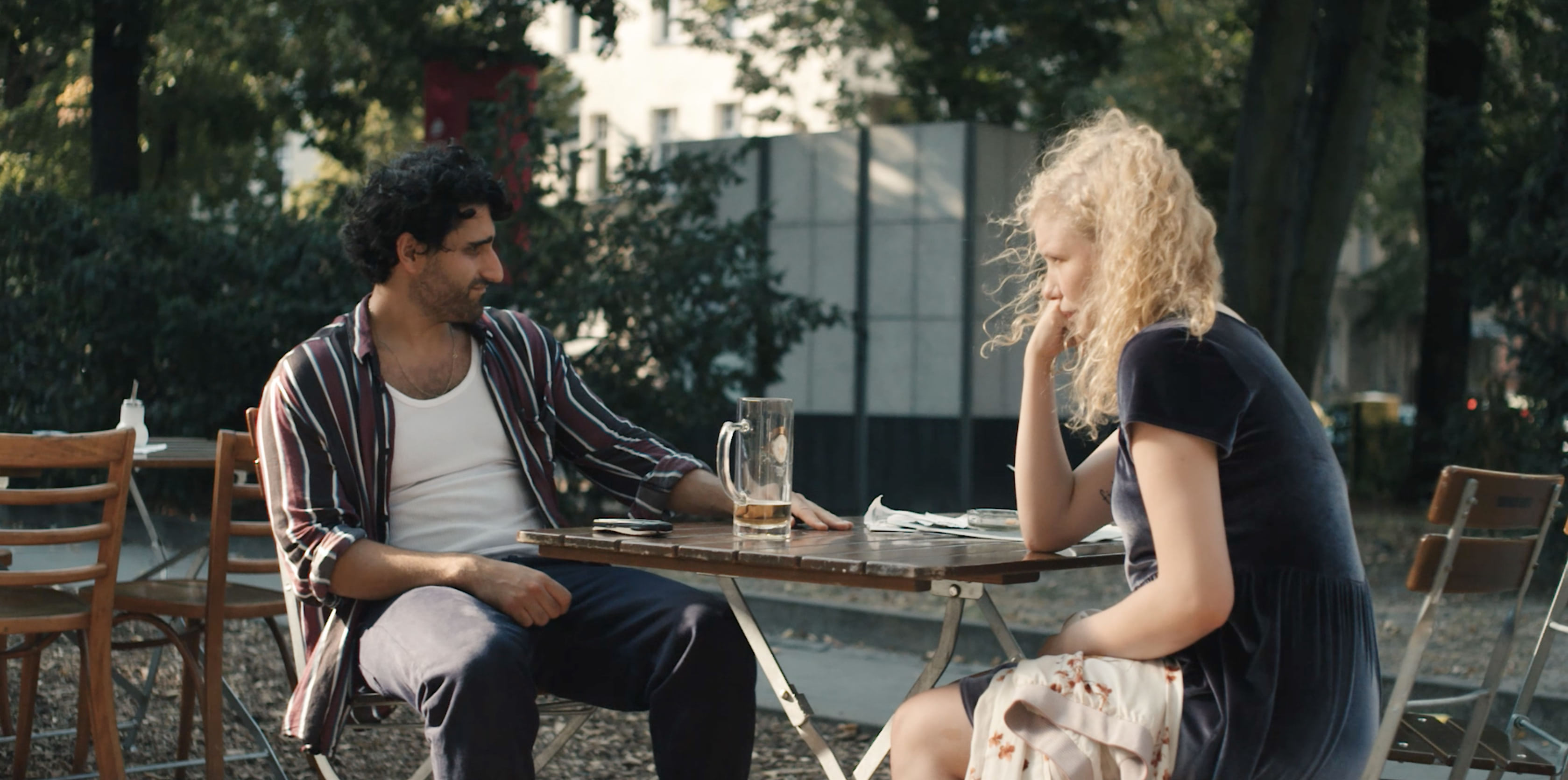 A man and a woman sitting at a table outside, the woman's hair is blowing in the wind.