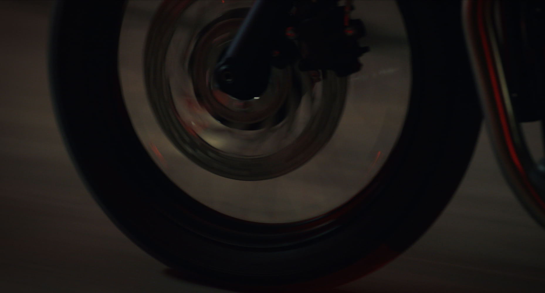 Detail of a motorcycle wheel driving over the ground.