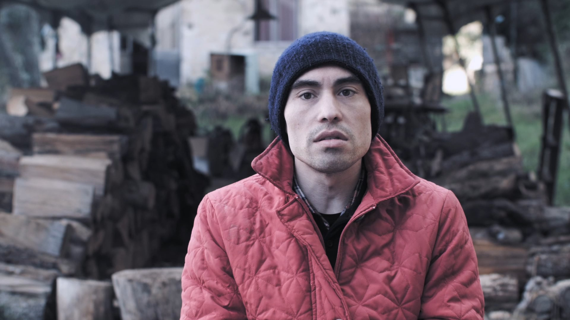 A man in a red jacket and a blue beanie is sitting outside in front of some firewood.