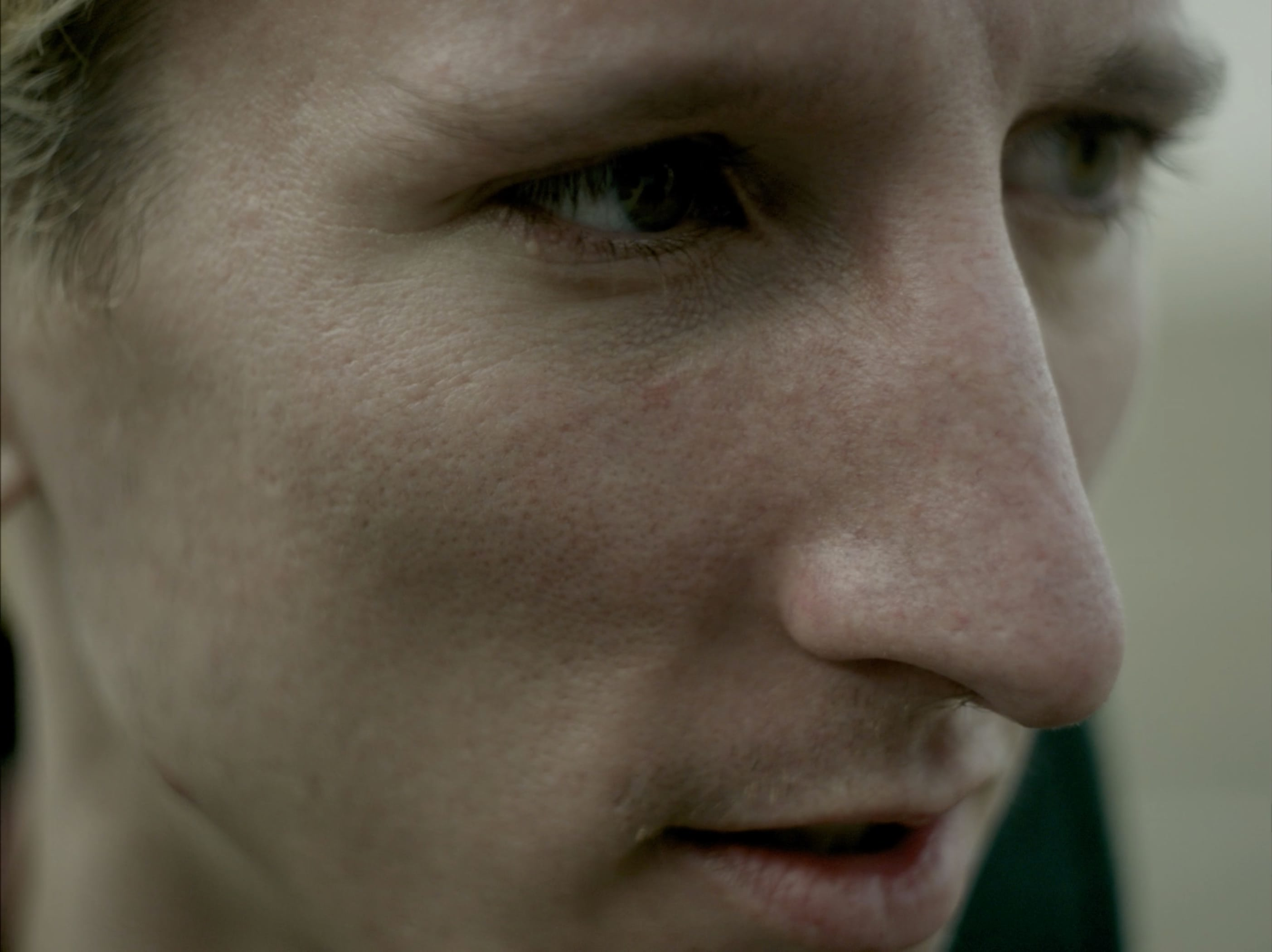 Close up of a young man outside looking off screen.