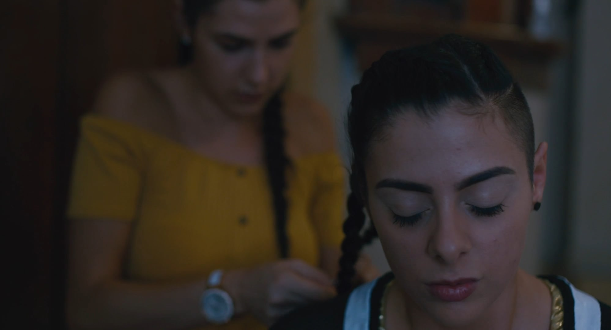 A young woman with her eyes closed has her hair braided by another woman behind her.