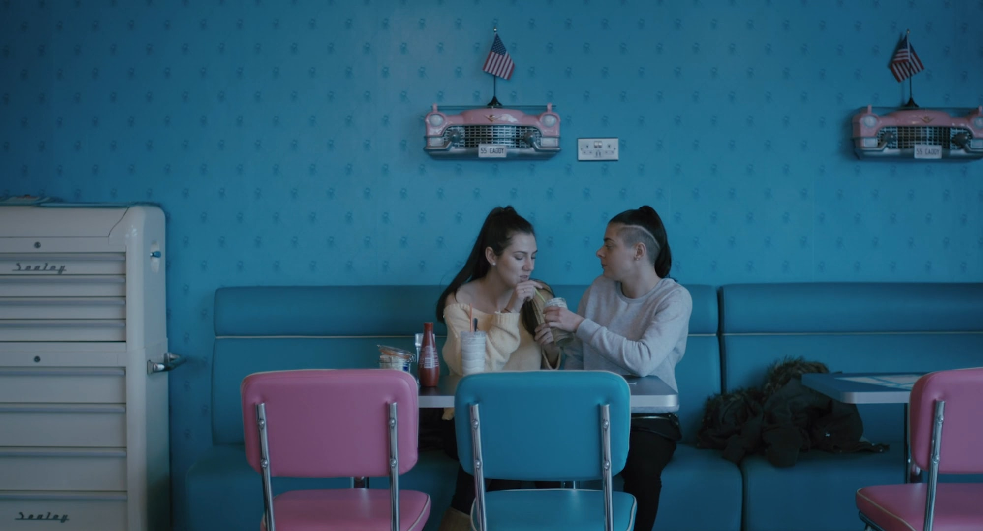 Two young women in an American diner drinking a milk shake and looking at each other.