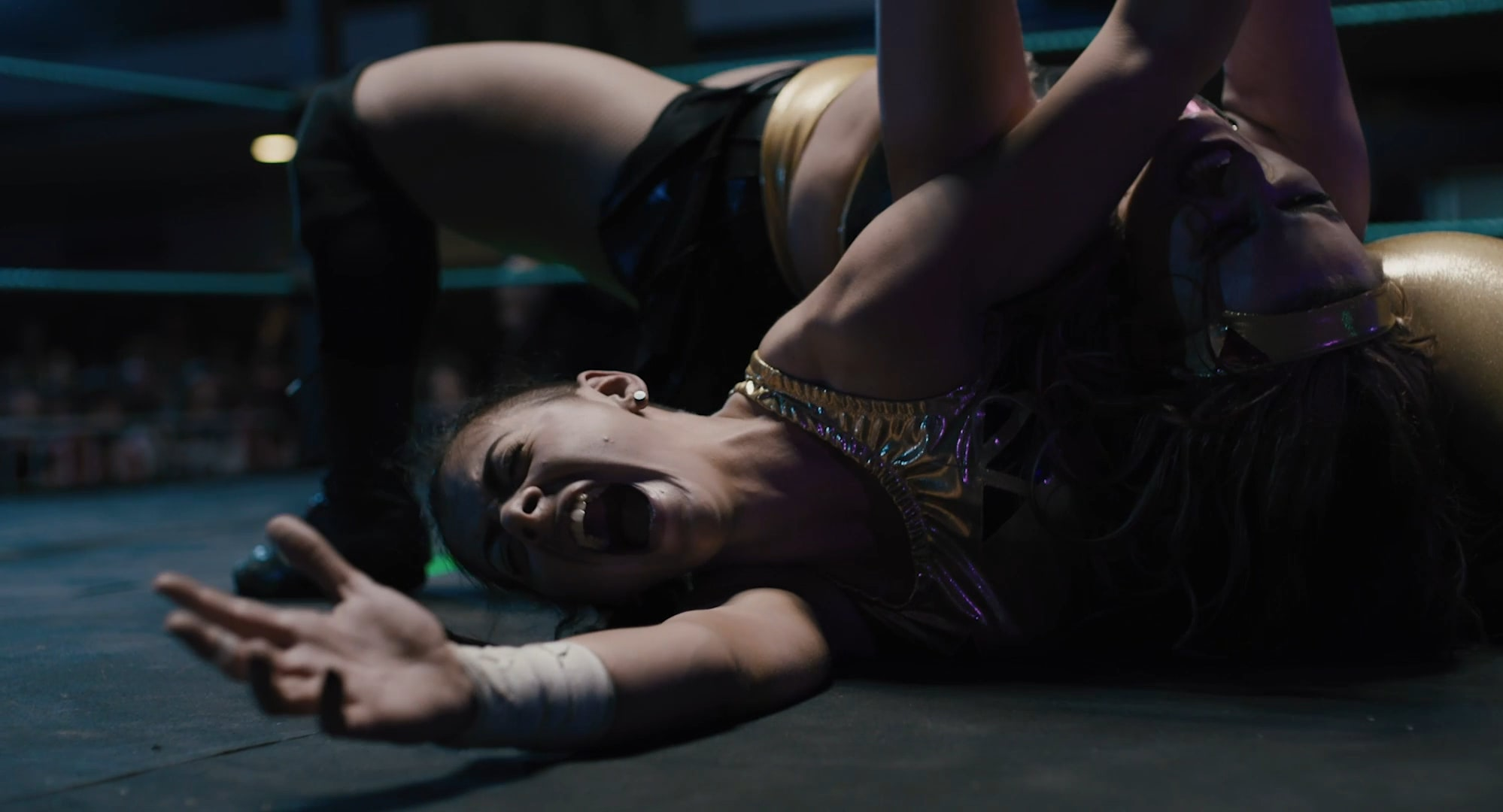 A young woman lying on the floor of the ring, screaming in pain, while another woman is on top of her.
