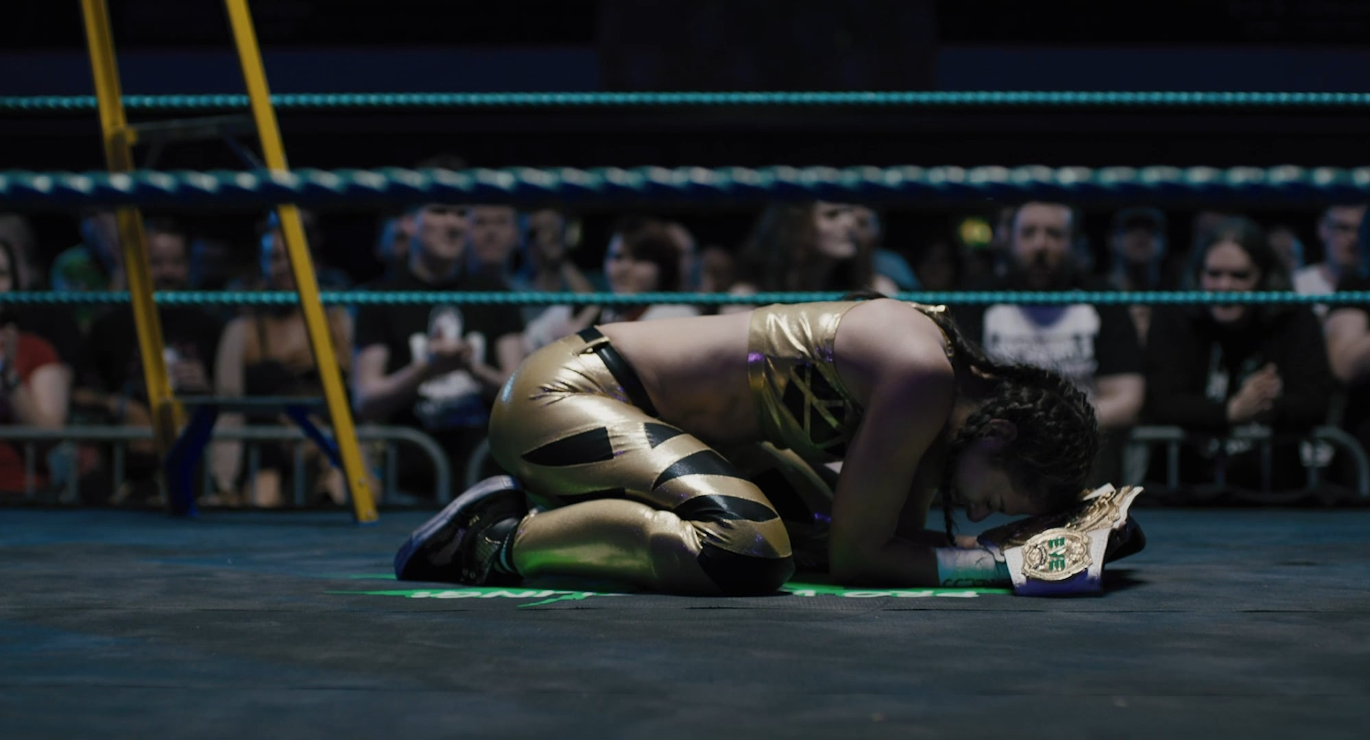 A young woman overcome with emotion kneeling in the wrestling ring, embracing a trophy
