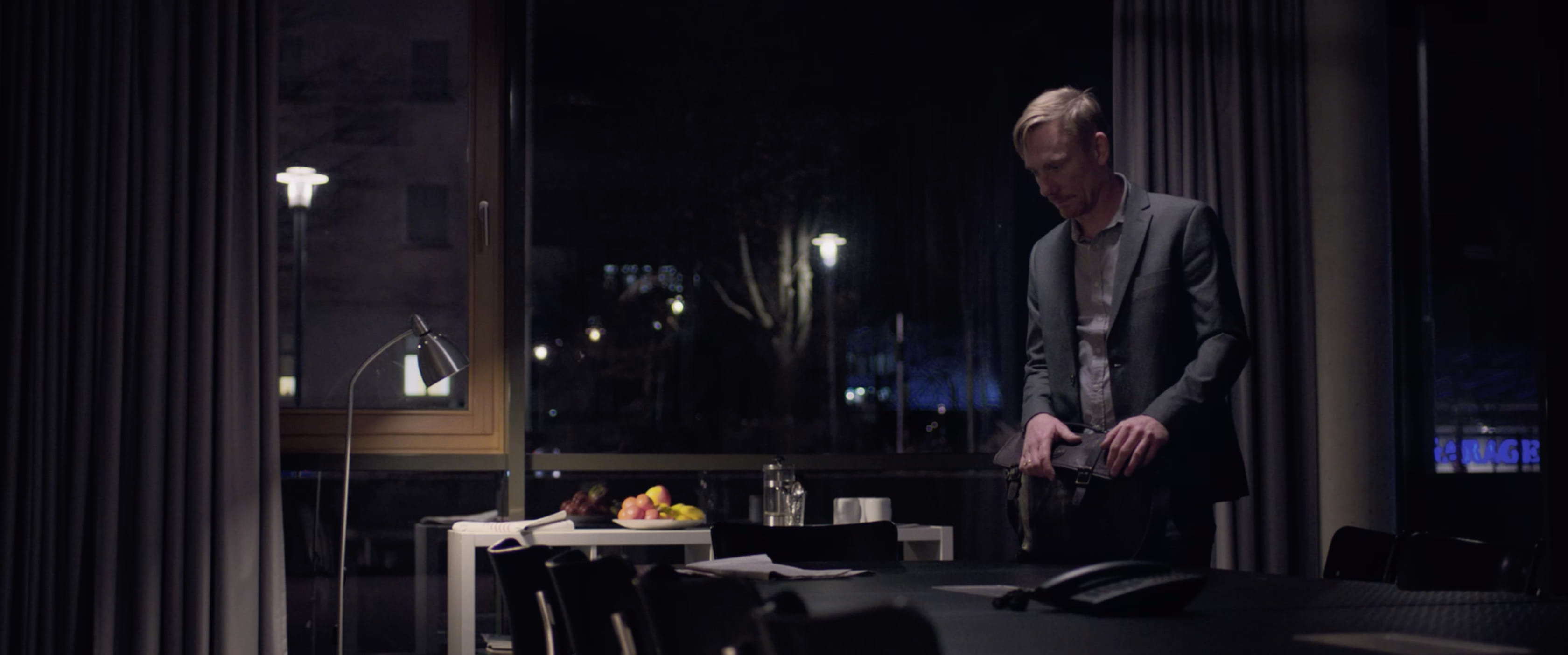 A man alone at night in a conference room, packing his briefcase absentmindedly.