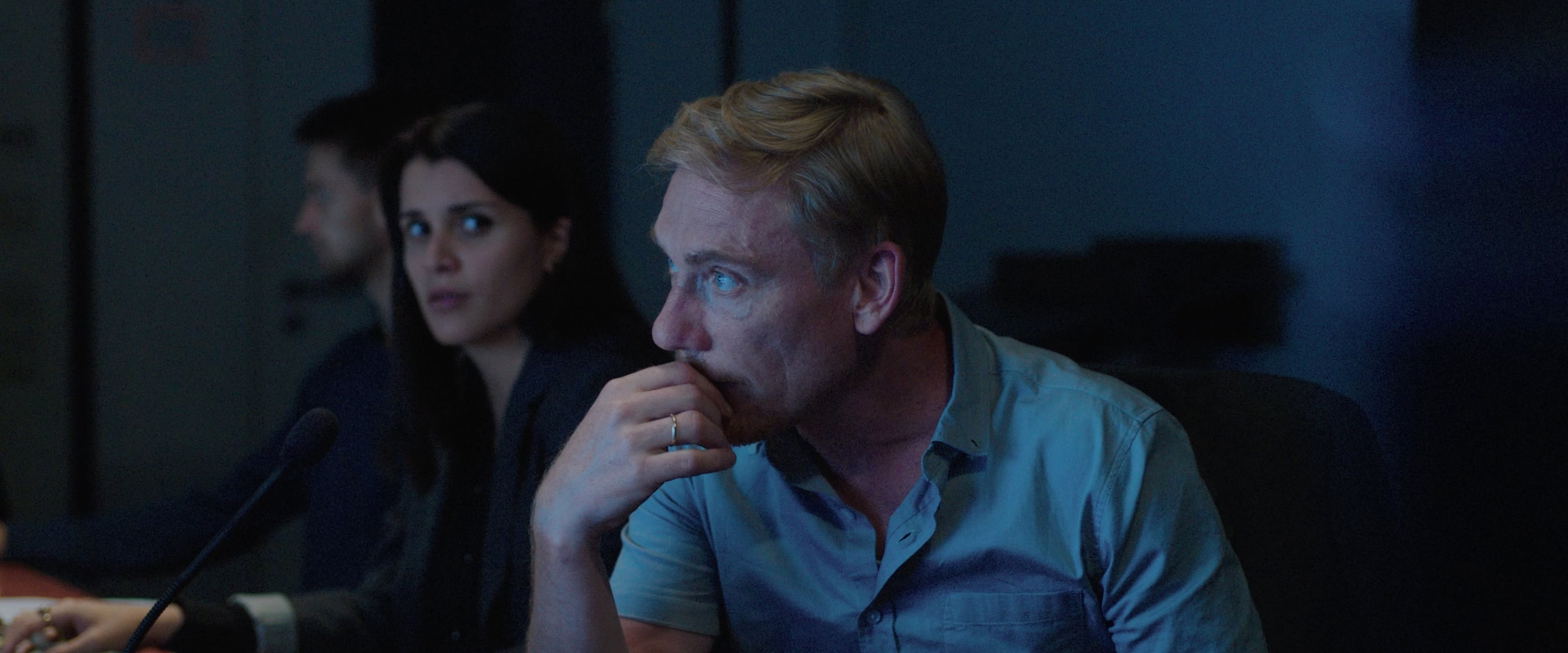 A man looking at a screen. The woman behind him looks towards him.