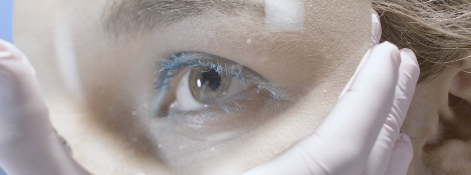 Detail of a young woman's eye with make up looking through a magnification glass.