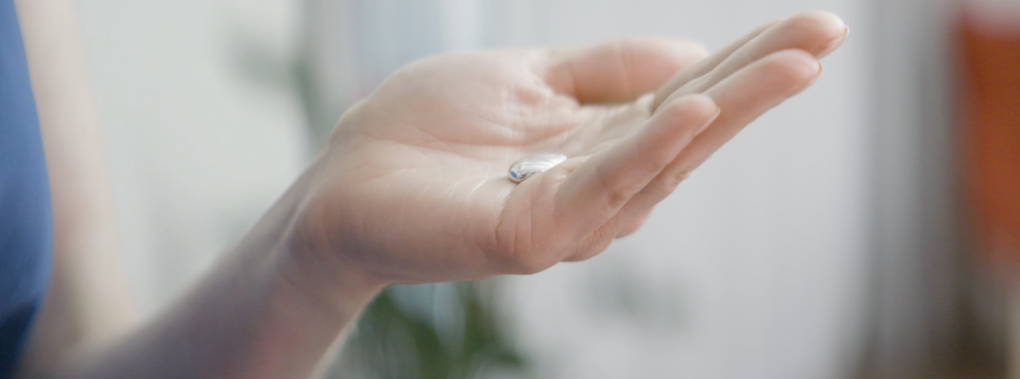 A small silver liquid in the palm of a woman's hand