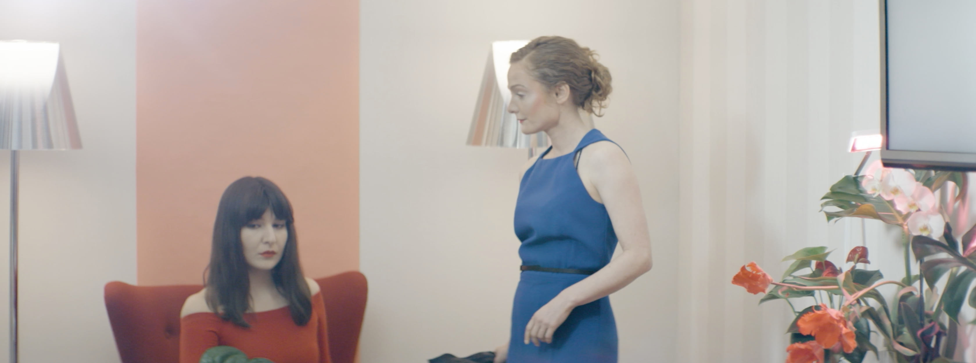Two women in a room with flowers, one is looking at the other.