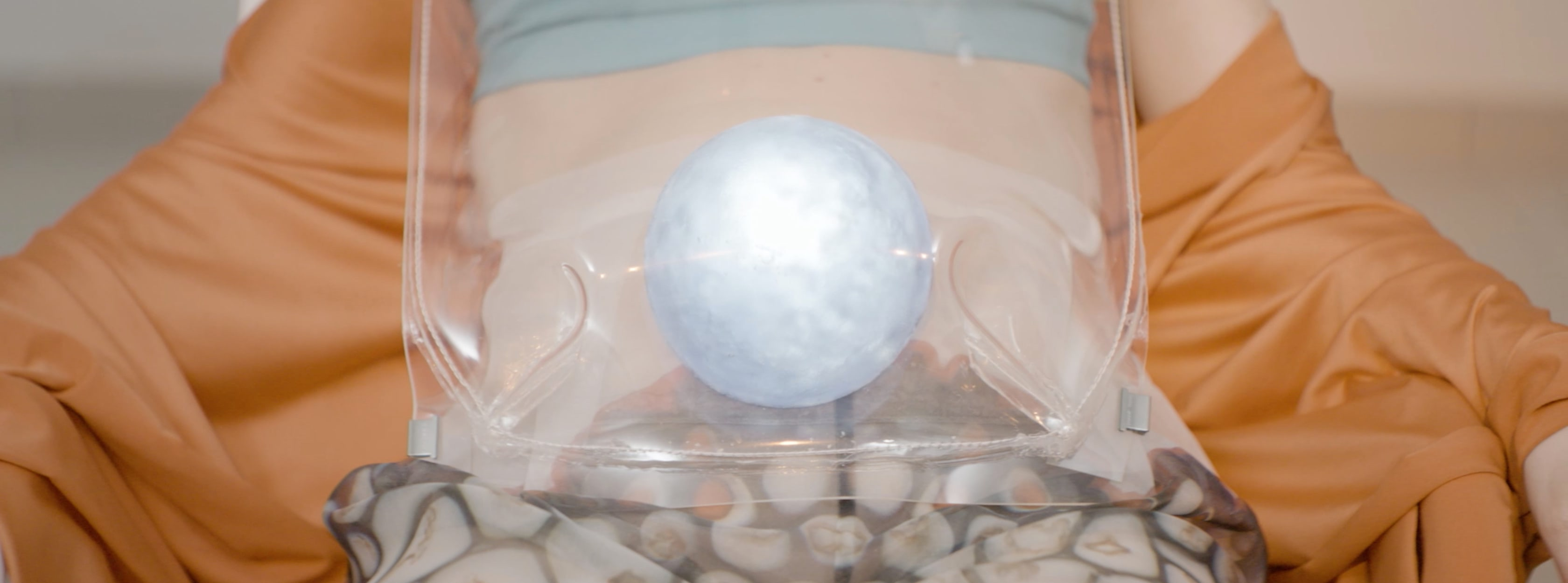 A blue shining orb is in a translucent bag placed on a woman's stomach.