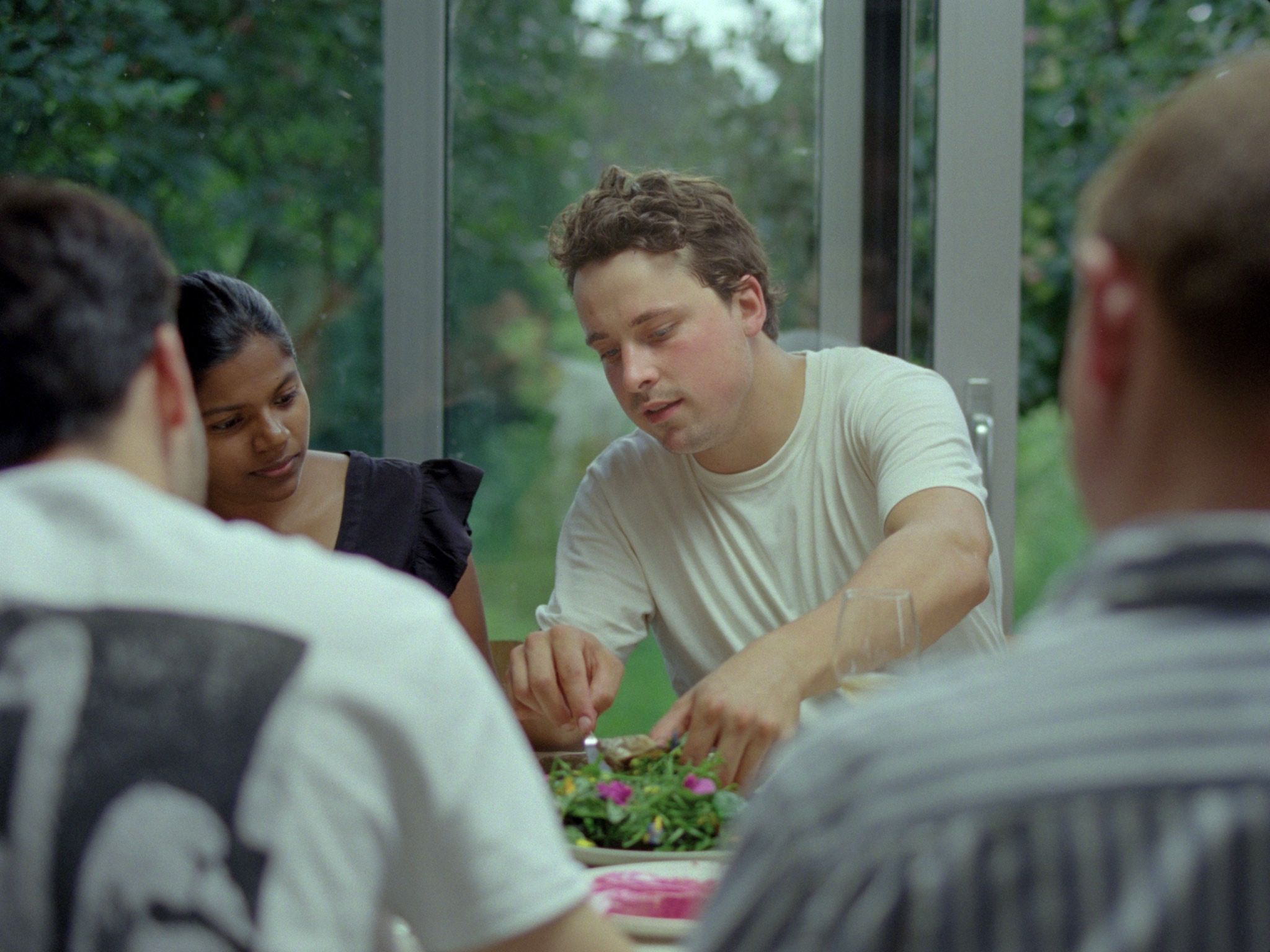 A young man surrounded by people sitting at a table, pointing towards the food on the middle of the table.