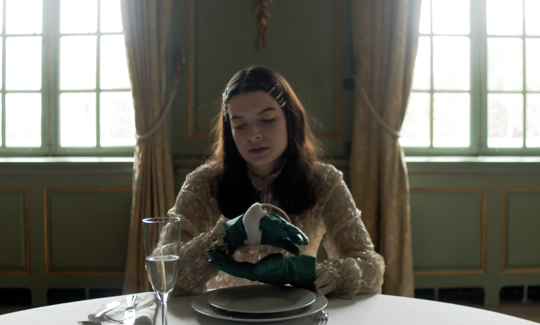 A young woman sitting at the table of an opulent green dining room, holding a white mouse in her hand.