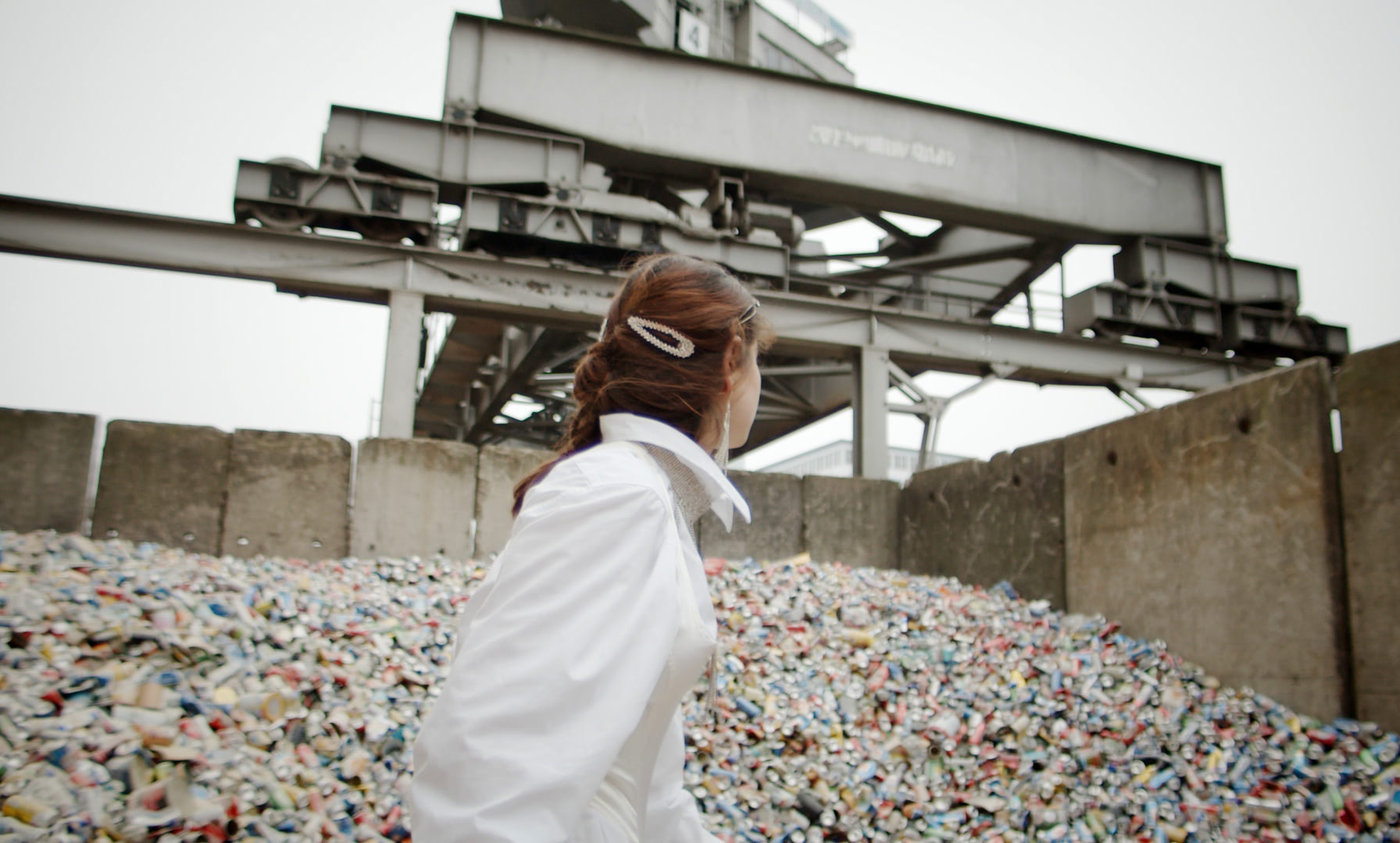 A young woman is standing in a recycling yard in front of a mountain of old discarded beer cans.