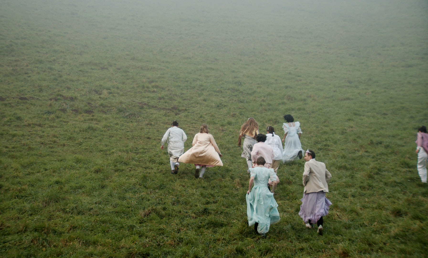 A crowd of people in white dresses running up a grassy hill in the fog.