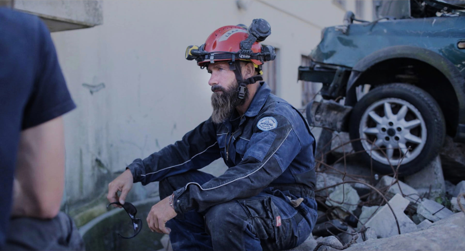 An exhausted man in an overall, wearing his helmet, sitting on some rubble in front of a smashed car.