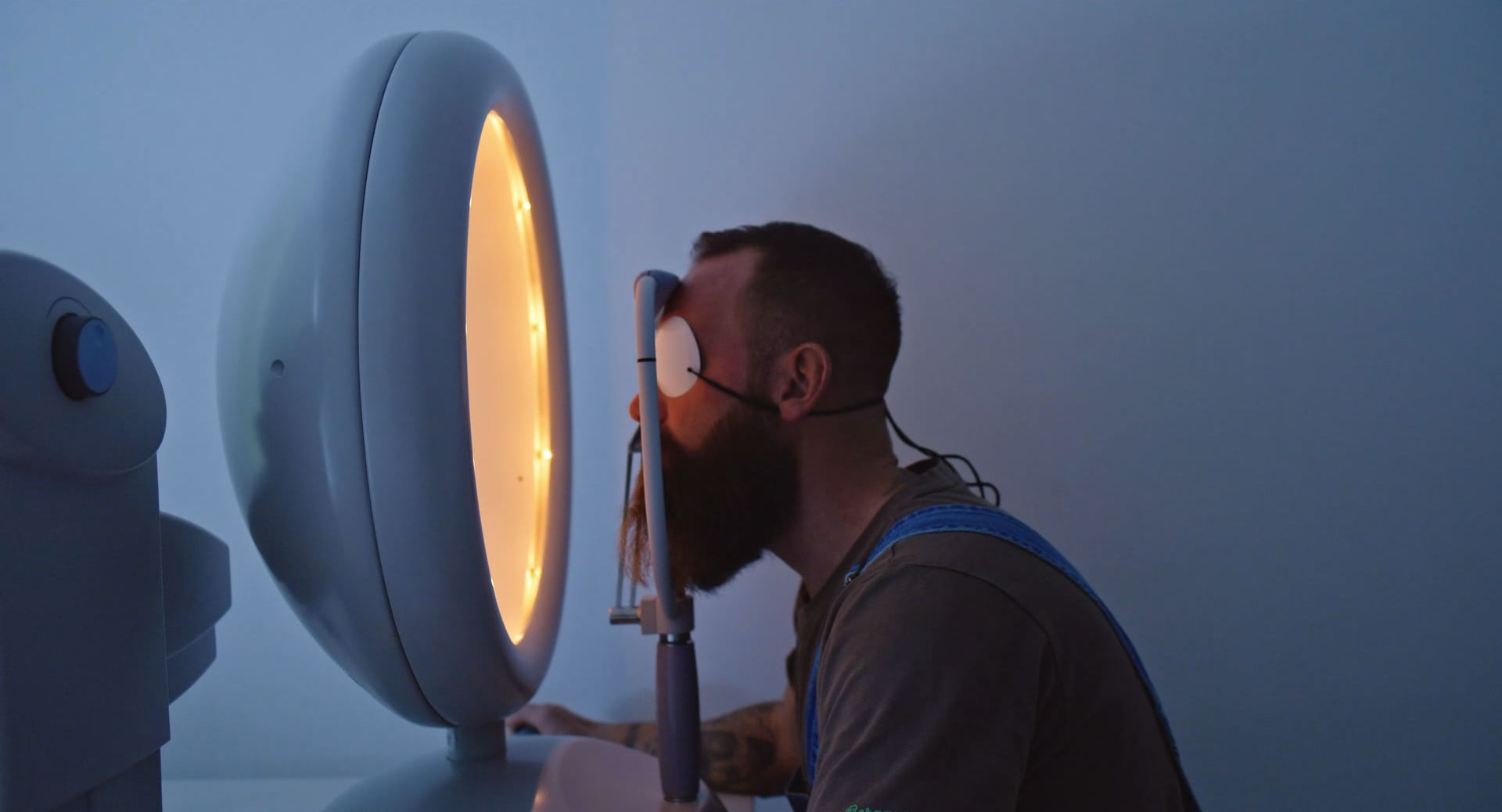 A man with an eye patch at a medical eye exam looking into a yellow light