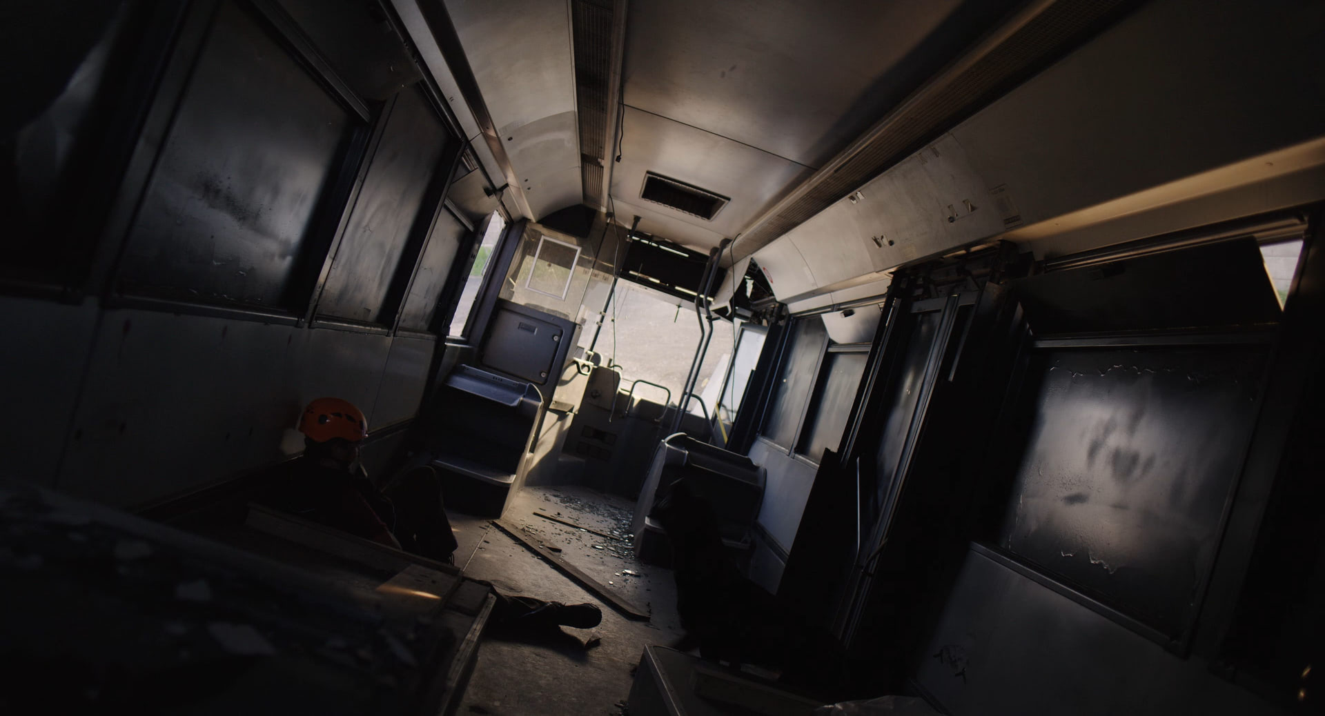 A person hiding inside the interior of an abandoned and broken down bus.