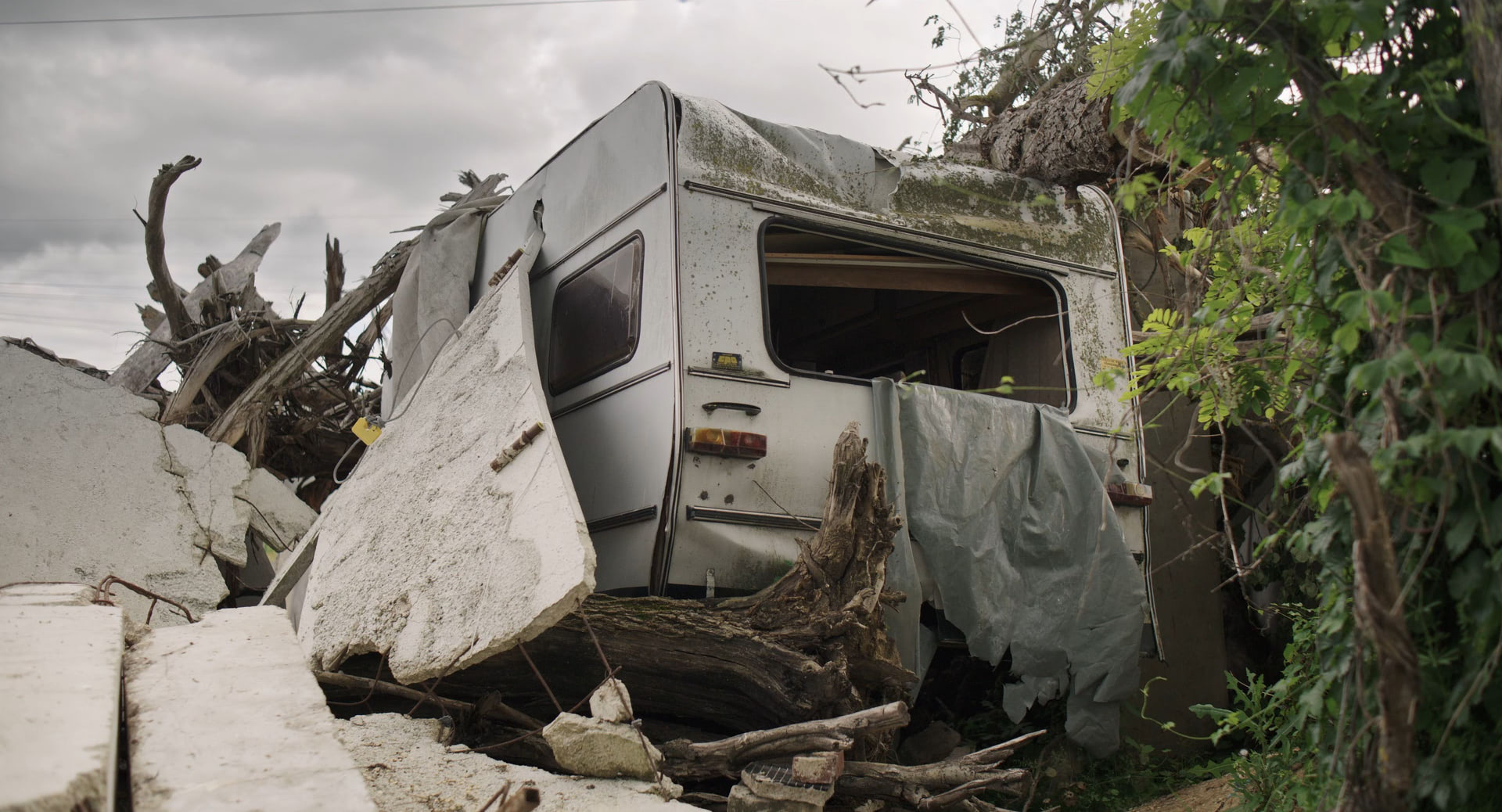 An old and destroyed caravan covered by wood and rubble