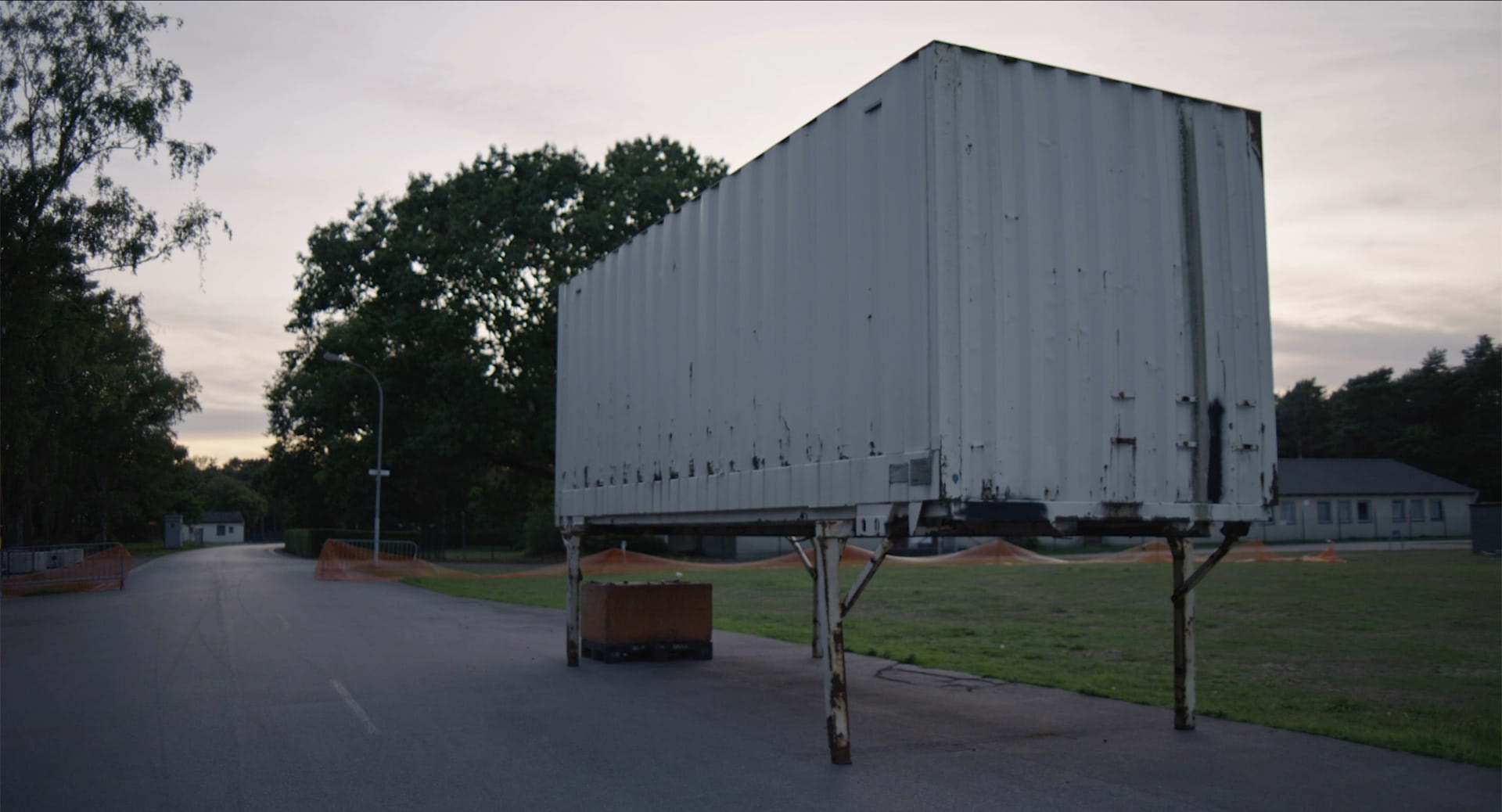 A trucking container sitting abandoned on a small dusk at magic hour.