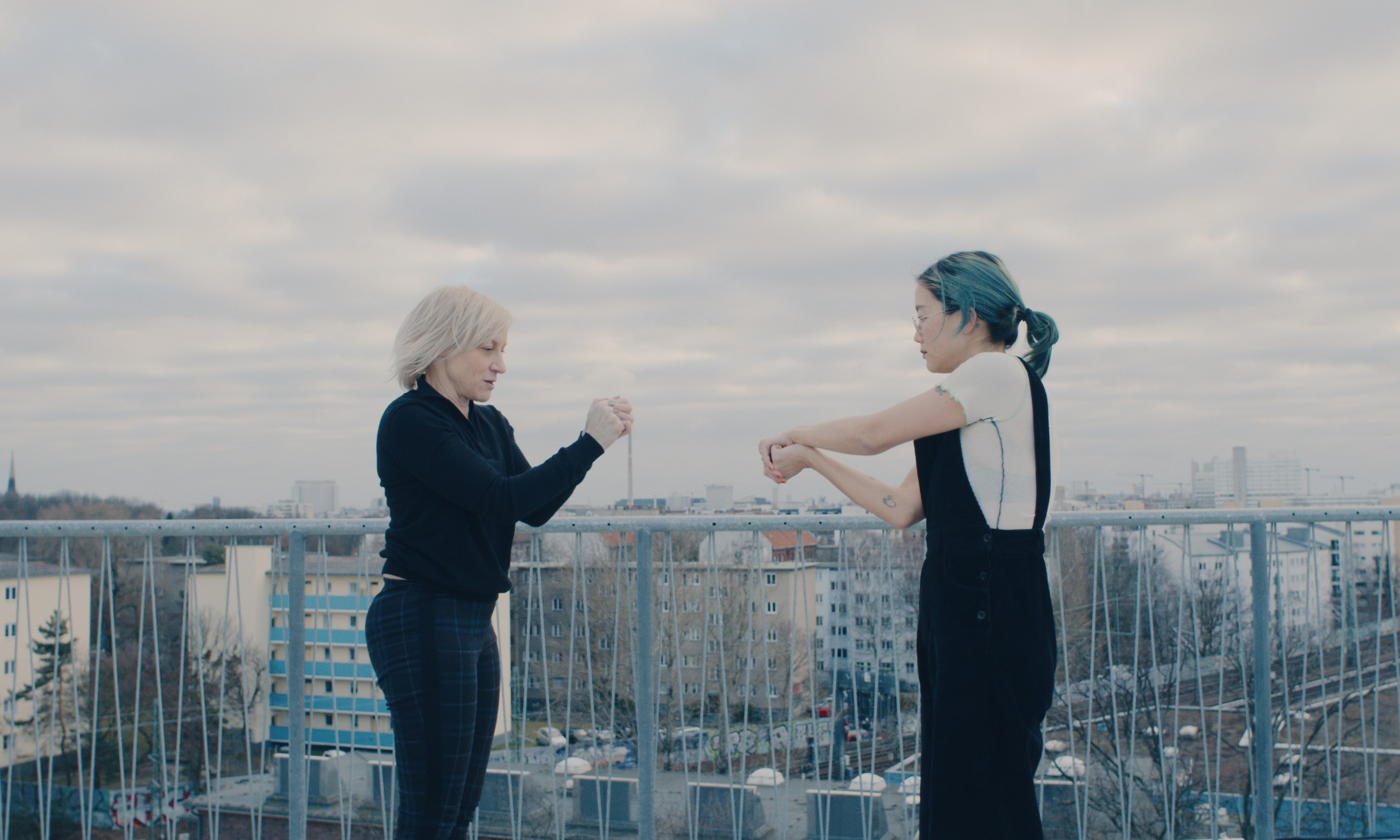 Christine Sun Kim and Meg Stuart dancing on a roof top, Berlin skyline in the background