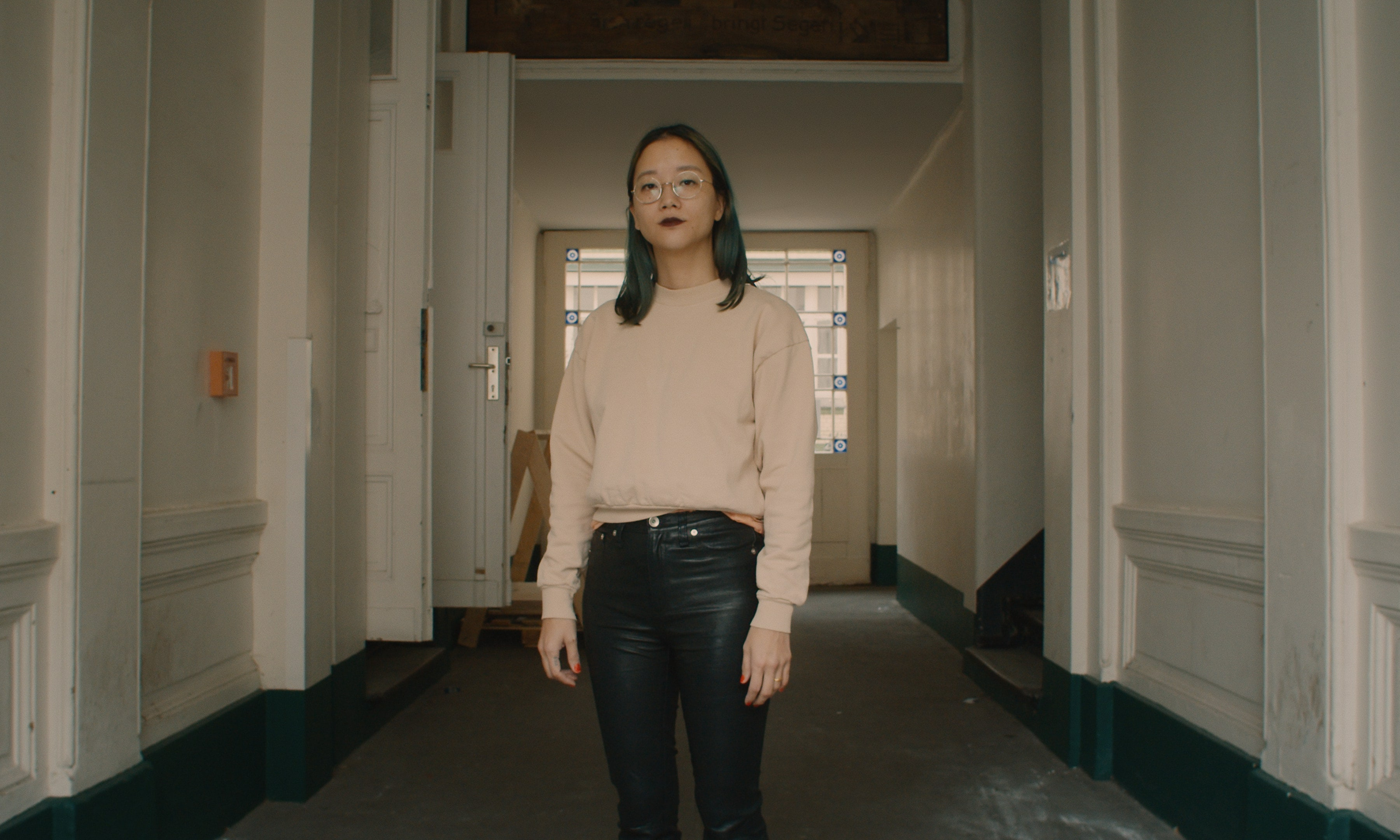 Christine Sun Kim standing in the hallway of an old building.