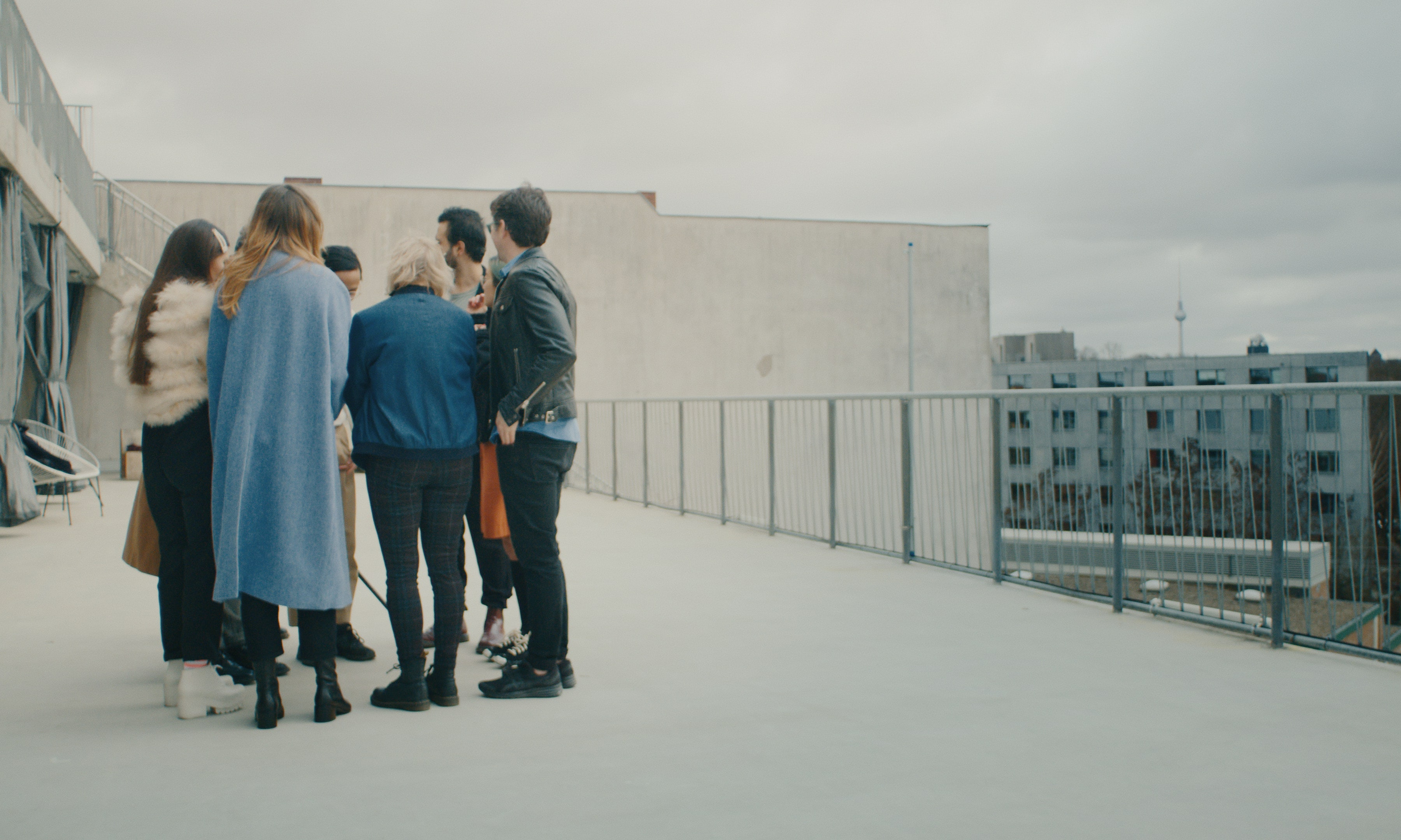 A group of people standing huddled together on a terrace, the Berlin TV Tower in the distance.