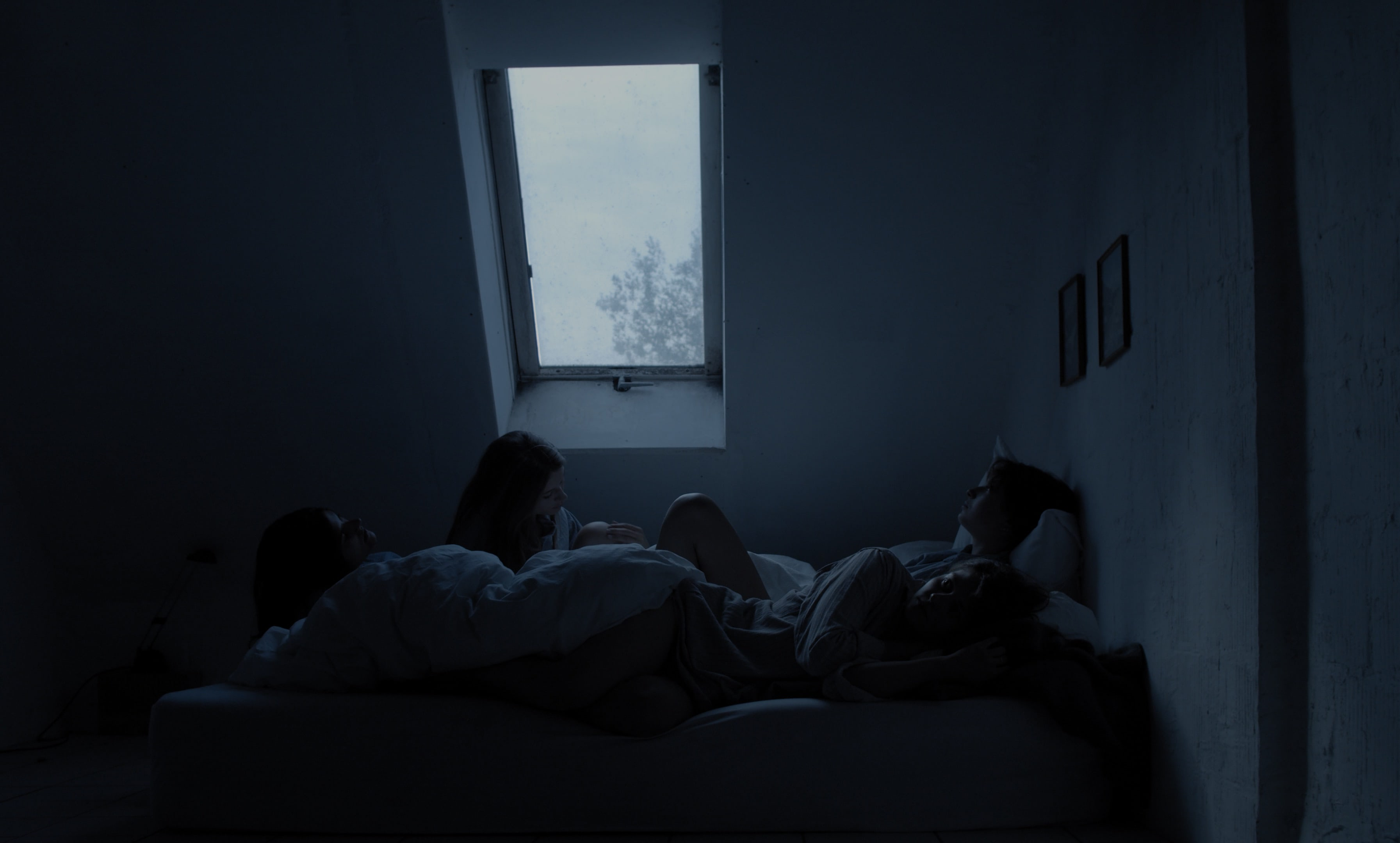 Four women lying in bed, waiting for something. Early morning light falls through the window.