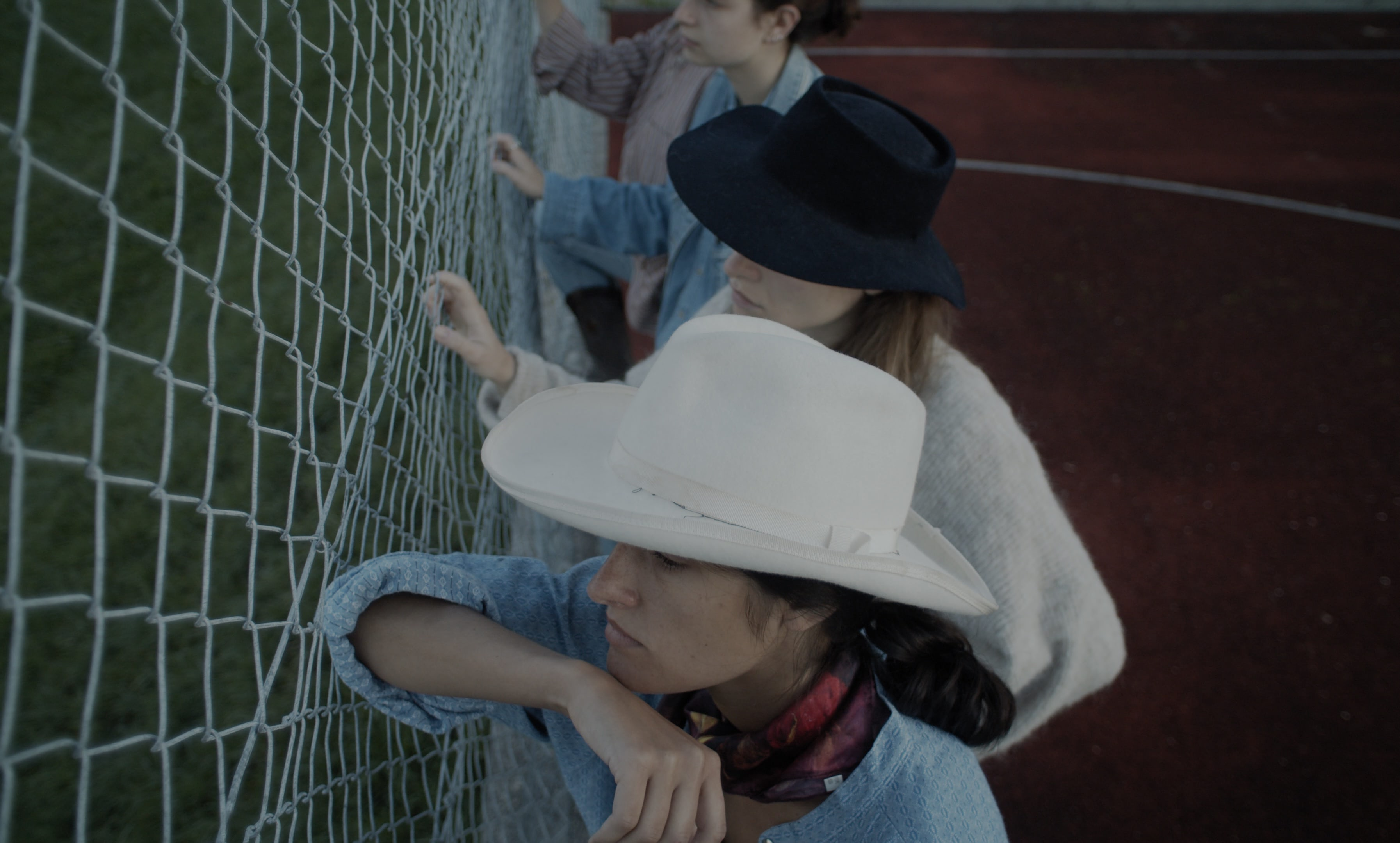 Four women, seen from above, leaning against a chain link fence. They are wearing cowboy hats.