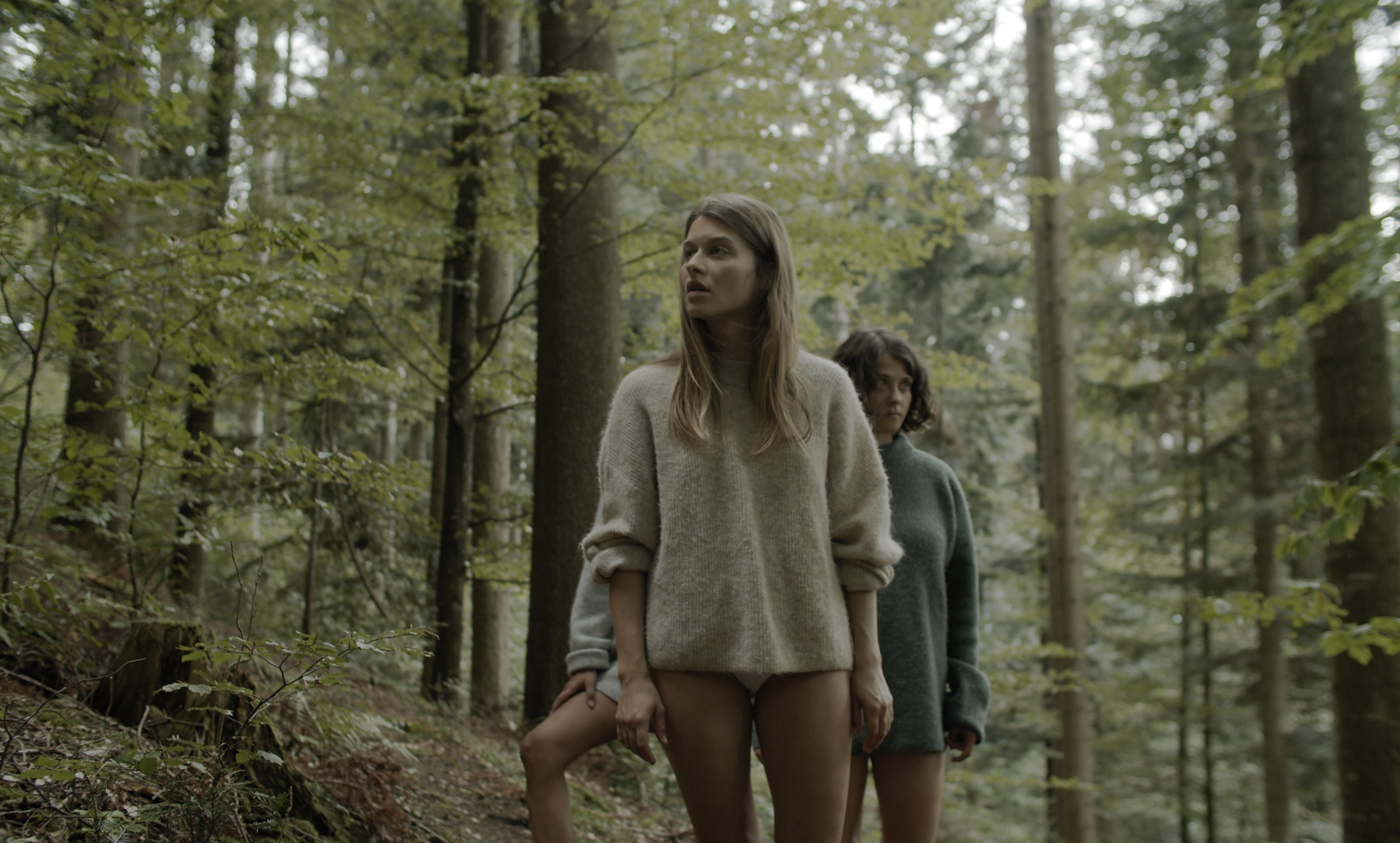 Three women with bare legs standing in a forest, looking around and searching.