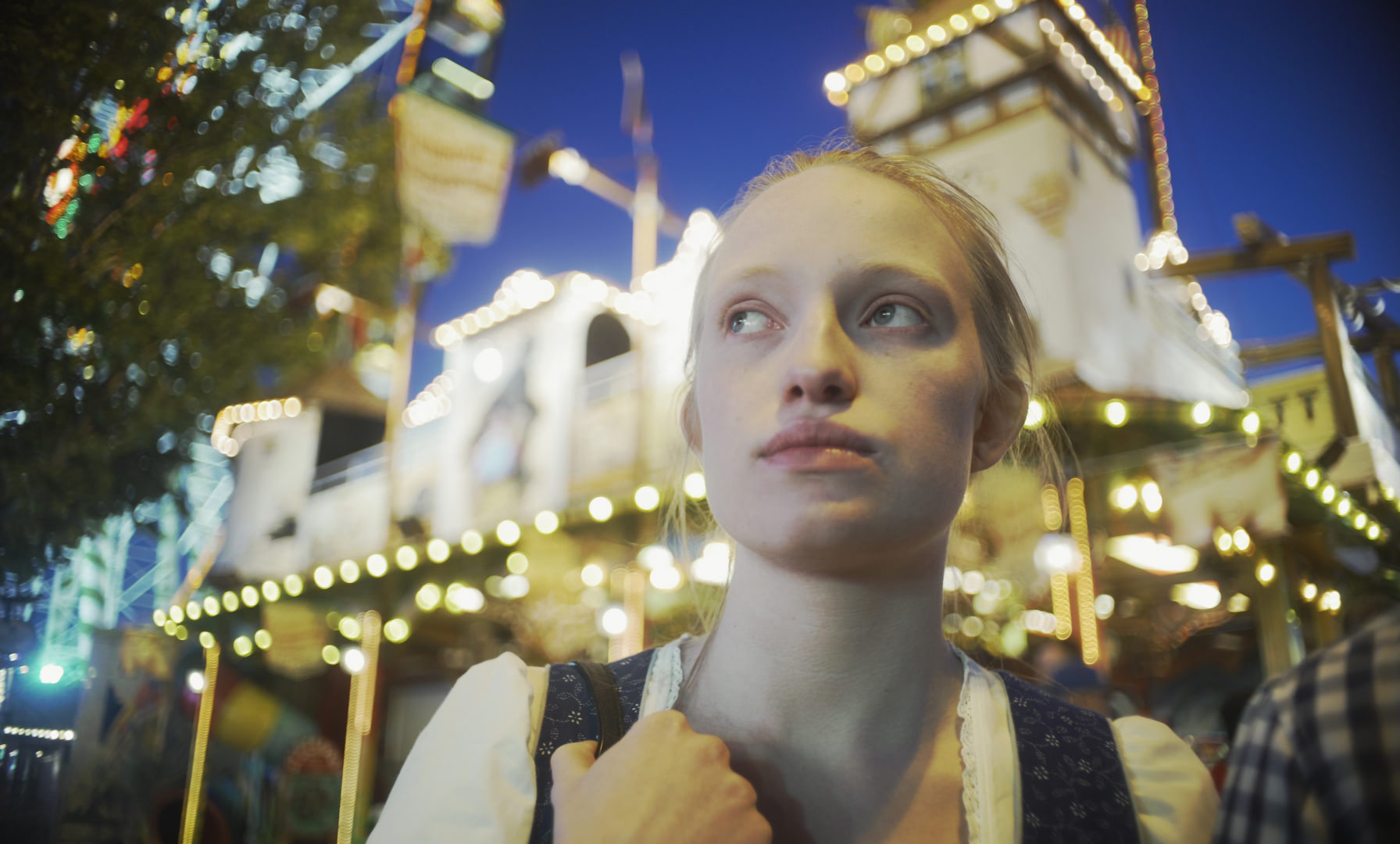 A young woman at an amusement park at night with colorful lights.
