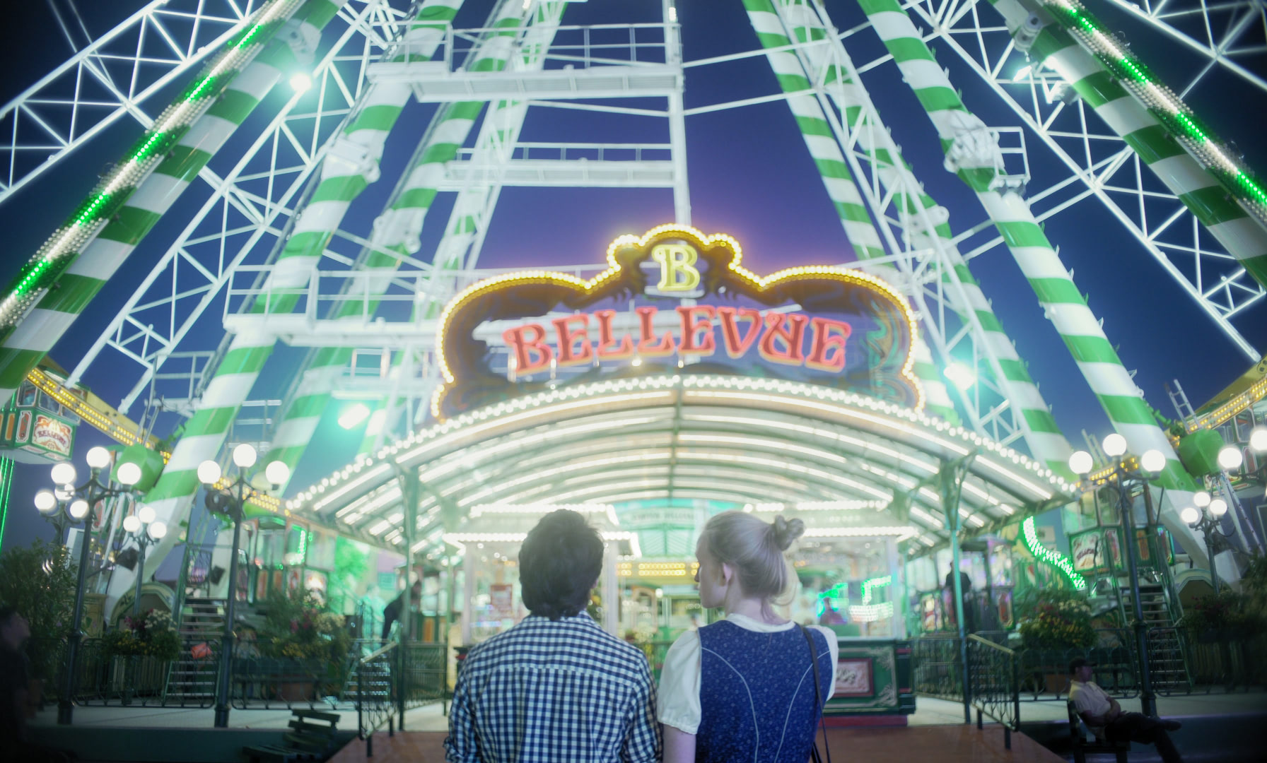 A young man and a woman are standing in front a Ferris wheel, looking at each other.